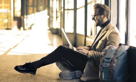 Man on laptop sitting on floor of airport