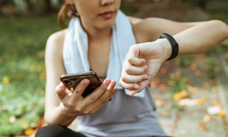 Woman with smartphone and fitness tracker wearable tech