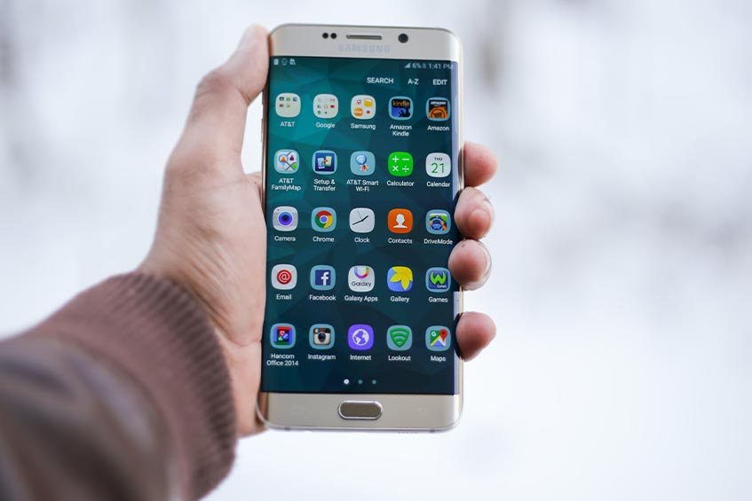 user holding Samsung Android smartphone with app tray open