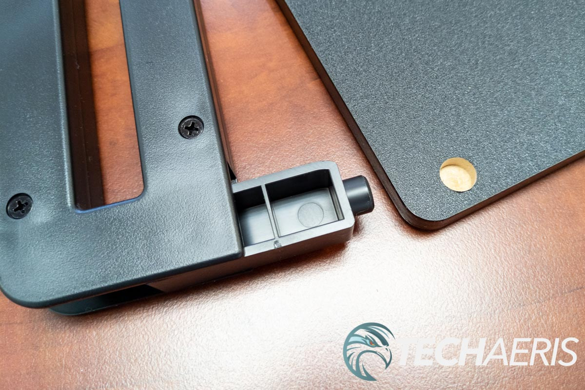 The plastic legs for the StarTech Monitor Riser Stand with Wireless Charging Pad fasten into a hole on the underside of the working surface