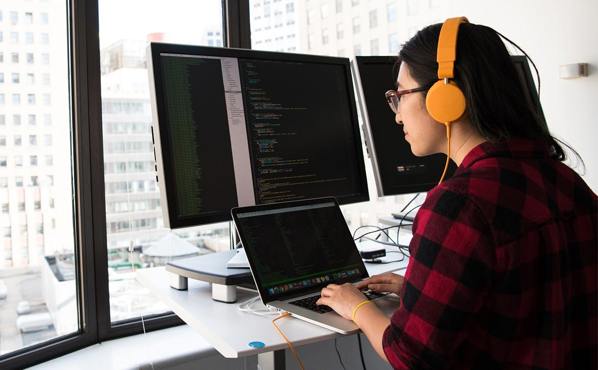 woman on laptop with monitors coding job