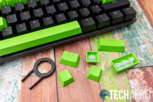 Some of the keys with the keycap puller included with the Razer PBT Keycap Upgrade Set